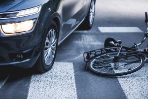 car-standing-on-the-pedestrian-path-with-the-downed-bicycle