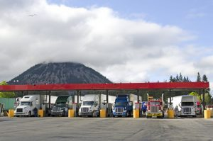 several-large-over-the-road-semi-trucks-fuel-up-at-a-fueling-station-truck-stop-in-california-300x199
