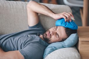frustrated-young-man-holding-ice-bag-on-his-head-while-lying-on-the-couch-at-home