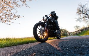 man-seated-on-motorcycle-on-the-road-during-sunrise