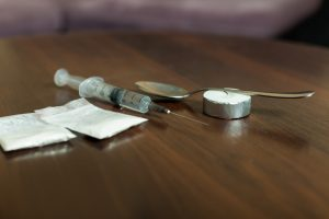 Drug, spoon and syringe on a table
