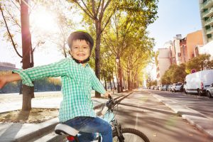 Happy boy cycling on bicycle lane in town