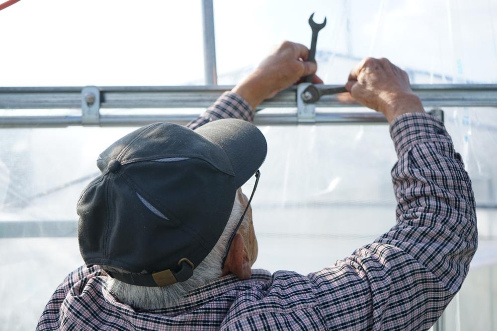 Senior man assembles greenhouse