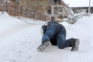 A man has slipped and has fallen down on ice
