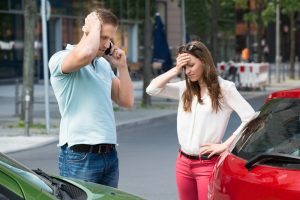 Sad Young Man Calling On Mobile Phone After Car Collision At Roadside