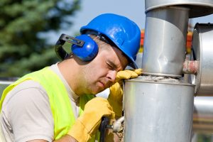 Tired worker fall asleep on oil pipe on plant
