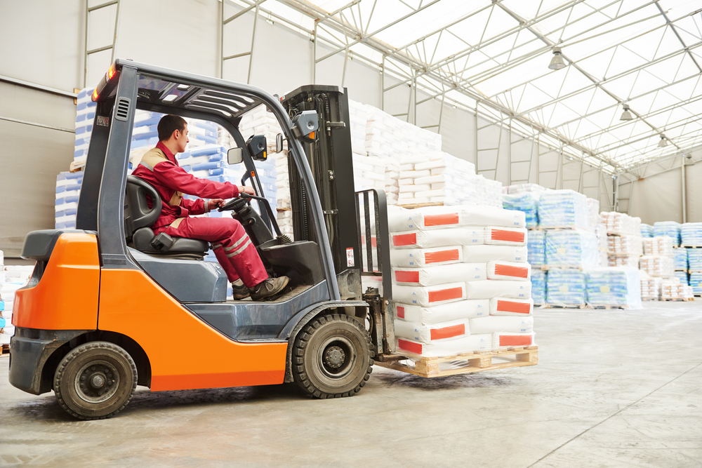 Forklift driver stacking pallets with cement packs by stacker loader
