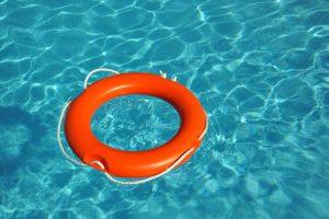 Orange lifebelt floating in blue water