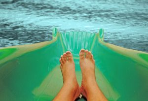 A pair of feet on a water slide about to land in a refreshing pool