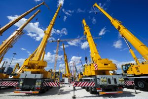 Mobile construction cranes with yellow telescopic arms and big tower cranes in sunny day with white clouds and deep blue sky on background