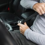 Closeup of man fastening seat belt in car