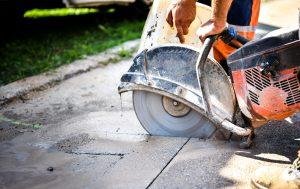 Construction worker cutting Asphalt paving stabs for sidewalk using a cut-off saw