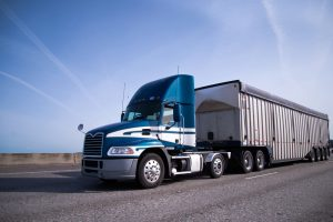 Contemporary big rig blue semi truck with high day cab and covered semi trailer for delivery bulk cargo moving on the wide highway with blue sky and little clouds on background