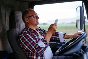 Senior man driving a truck and texting on a mobile phone