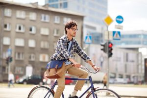 young hipster man with shoulder bag and earphones riding fixed gear bike on city street