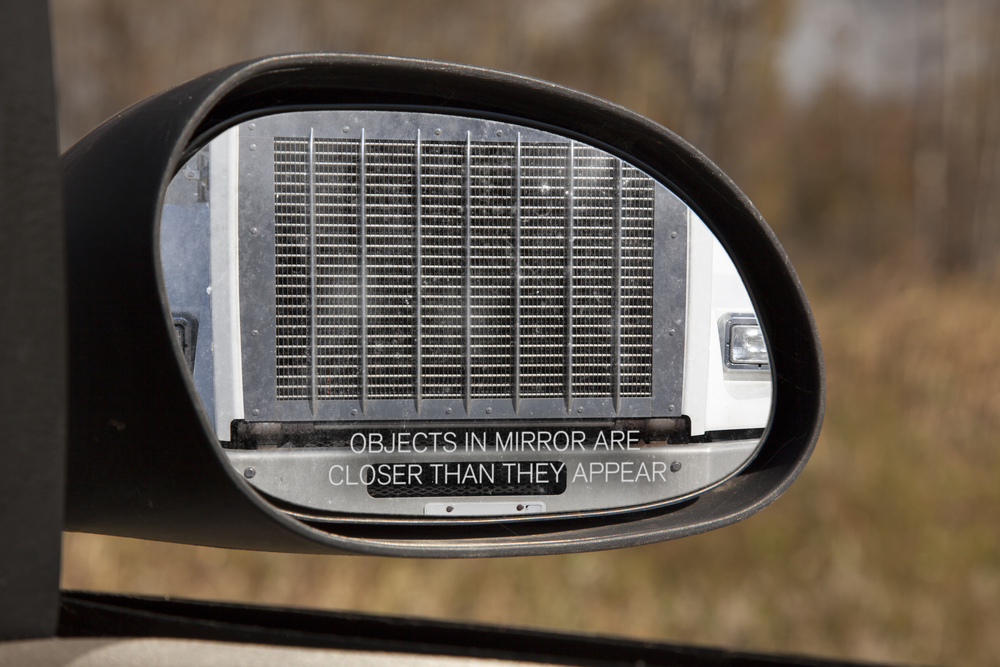 Looking through the rear view mirror you see the front grill of a large truck, obviously too close for comfort