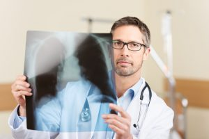Portrait of serious mature doctor holding X-ray report in hospital
