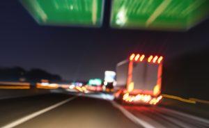 Blurred motion of defocused semi truck speeding on highway under street signs