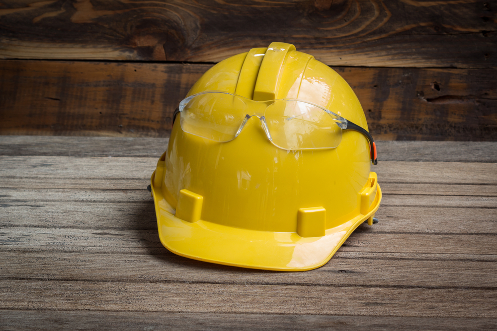Hard Hat and safety glasses on wooden background