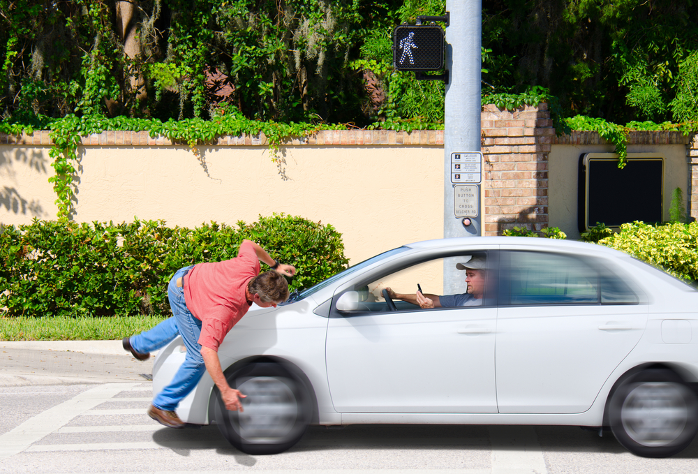 A man that is texting while driving runs over a pedestrian