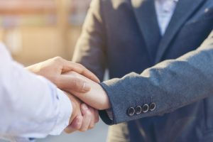 closeup of two men shaking hands