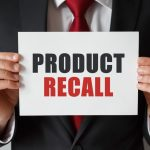 man holding product recall sign