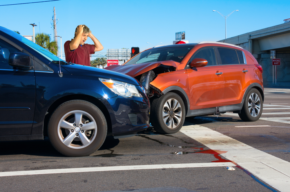 upset man standing behind car crash at intersection