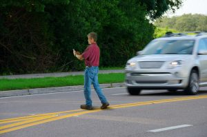 distracted man on his phone crossing the street about to be hit by a car