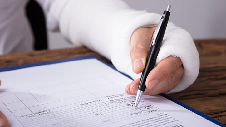 person with cast on arm signing a medical document
